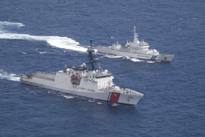 In this photo provided by U.S. Coast Guard, Coast Guard cutter Munro, bottom, and Japan Coat Guard patrol vessel Large Aso transit together in formation during a maritime engagement in the East China Sea on Aug. 25, 2021. China's defense ministry protested Saturday, Aug. 28, 2021 the passage of a U.S. Navy warship and Coast Guard cutter through the waters between China and Taiwan, a self-governing island claimed by China. (U.S. Coast Guard via AP)