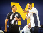 Michigan head coach Juwan Howard, right, speaks with game official Bo Boroski courtside in the first half of an NCAA college basketball game against Oakland at Crisler Center in Ann Arbor, Mich., Sunday, Nov. 29, 2020. (AP Photo/Tony Ding)