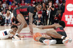 Connecticut guard Alterique Gilbert, left, reaches under Houston guard DeJon Jarreau, middle, for the loose ball as center Brison Gresham, right, grabs it from the floor during the first half of an NCAA college basketball game Thursday, Jan. 23, 2020, in Houston. (AP Photo/Michael Wyke)