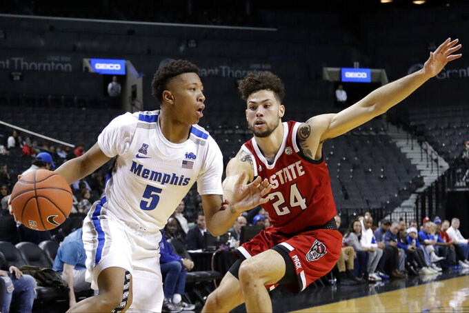 Memphis' Boogie Ellis (5) drives past North Carolina State's Devon Daniels (24) during the first half of an NCAA college basketball game in the Barclays Classic, Thursday, Nov. 28, 2019, in New York. (AP Photo/Frank Franklin II)