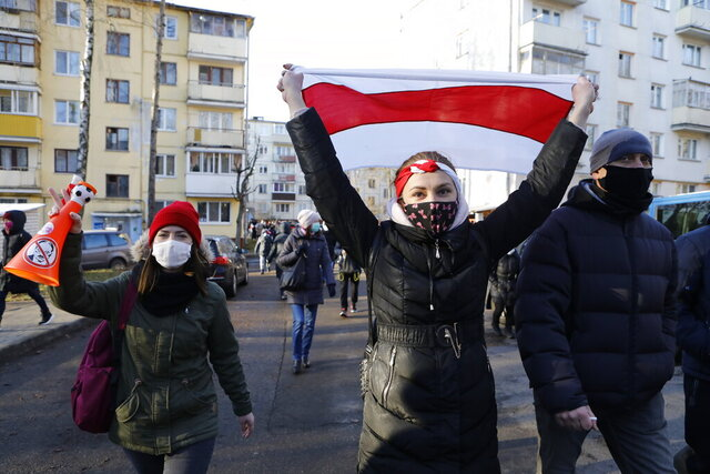 Demonstrators wearing face masks to help curb the spread of the coronavirus, at right one waves an old Belarusian national flag, during an opposition rally to protest the official presidential election results in Minsk, Belarus, Sunday, Dec. 6, 2020. Protests in Belarus have continued for almost four months after President Alexander Lukashenko won his sixth term in office in an election the opposition says was rigged. (AP Photo)
