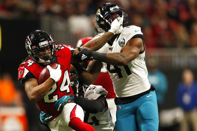 Atlanta Falcons running back Devonta Freeman (24) runs past Jacksonville Jaguars linebacker Josh Allen (41during the first half of an NFL football game, Sunday, Dec. 22, 2019, in Atlanta. (AP Photo/John Bazemore)