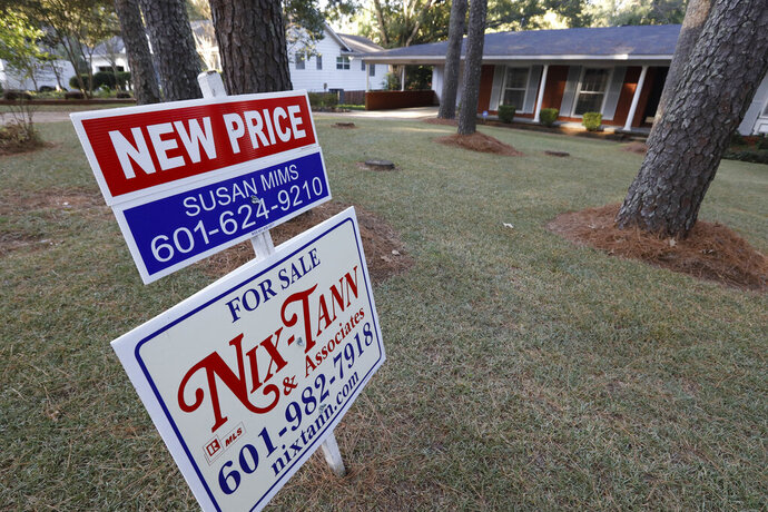 FILE - In this Sept. 25, 2019, file photo a sign indicates a new selling price for a house sits atop a realtor's sign in Jackson, Miss. On Thursday, Nov. 14, Freddie Mac reports on this week's average U.S. mortgage rates. (AP Photo/Rogelio V. Solis, File)