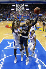 UNC Greensboro's Kaleb Hunter (44) gets past Kansas' Ochai Agbaji (30) for a shot during the first half of an NCAA college basketball game Friday, Nov. 8, 2019, in Lawrence, Kan. (AP Photo/Charlie Riedel)
