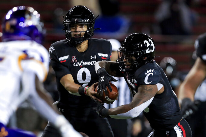 Cincinnati quarterback Desmond Ridder hands off the ball to running back Gerrid Doaks, right, during the first half of the team's NCAA college football game against East Carolina, Friday, Nov. 13, 2020, in Cincinnati. (AP Photo/Aaron Doster)