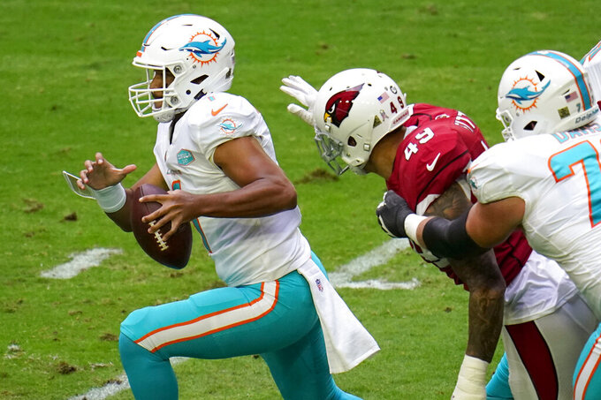 Miami Dolphins quarterback Tua Tagovailoa (1) tries to escape the reach of Arizona Cardinals linebacker Kylie Fitts (49) during the first half of an NFL football game, Sunday, Nov. 8, 2020, in Glendale, Ariz. (AP Photo/Ross D. Franklin)