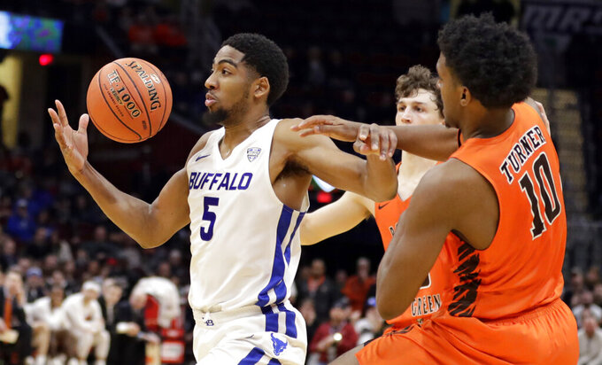 Buffalo's CJ Massinburg (5) drives past Bowling Green's Justin Turner (10) during the second half of an NCAA college basketball game for the Mid-American Conference men's tournament title Saturday, March 16, 2019, in Cleveland. Buffalo won 87-73. (AP Photo/Tony Dejak)