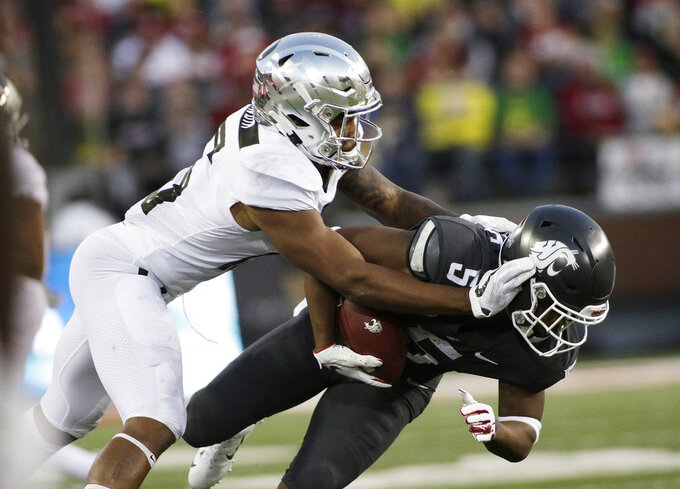 Oregon cornerback Deommodore Lenoir, left, tackles Washington State wide receiver Travell Harris (5) during the first half of an NCAA college football game in Pullman, Wash., Saturday, Oct. 20, 2018. (AP Photo/Young Kwak)