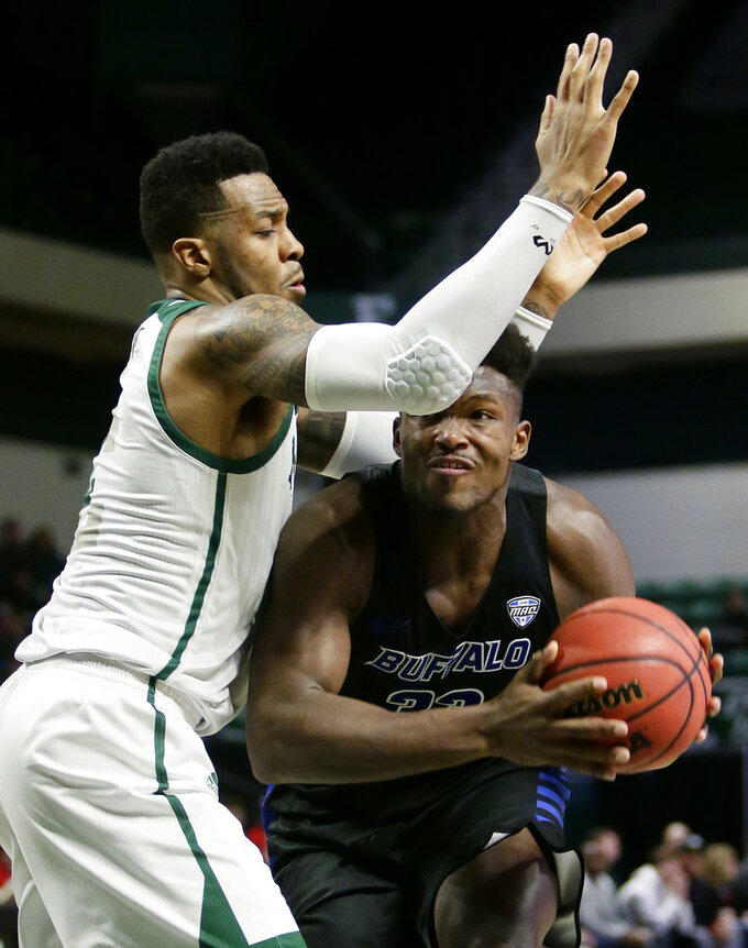 Buffalo forward Nick Perkins (33) is guarded by Eastern Michigan center James Thompson IV, left, while trying to take a shot during the first half of an NCAA college basketball game Friday, Jan. 4, 2019, in Ypsilanti, Mich. (AP Photo/Duane Burleson)