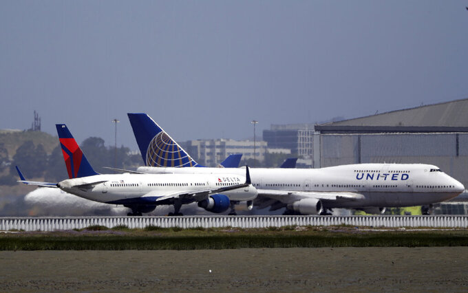 FILE - This July 11, 2017, file photo, shows a Delta Air Lines jet and a United Airlines plane at San Francisco International Airport in San Francisco. The Trump administration said Friday, June 5, 2020, it will let Chinese airlines operate a limited number of flights to the U.S., backing down from a threat to ban the flights. The decision came one day after China appeared to open the door to U.S. carriers United Airlines and Delta Air Lines resuming one flight per week each into the country. (AP Photo/Marcio Jose Sanchez, File)