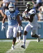 Wake Forest receiver Donavon Greene (7) pulls in a 39-yard pass quarterback Sam Hartman (10) ahead of North Carolina's Jeremiah Gimmel (44)  in the first half of an NCAA college football game Saturday, Nov. 14, 2020, in Chapel Hill, N.C.  (Robert Willett/The News & Observer via AP)