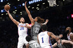 Philadelphia 76ers guard Ben Simmons (25) goes to the basket against Brooklyn Nets forward Nicolas Claxton (33) during the first half of an NBA basketball game, Monday, Jan. 20, 2020, in New York. (AP Photo/Mary Altaffer)