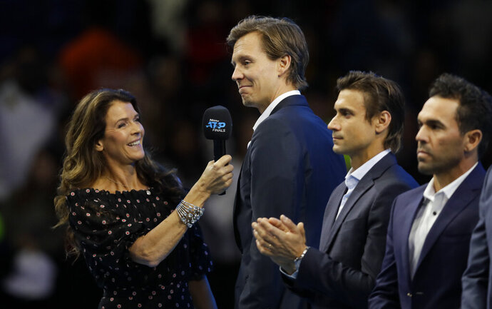 Tomas Berdych of the Czech Republic, second left, is interviewed by television presenter Annabel Croft as he stands on court during a ceremony to honour former tennis players at the ATP World Tour Finals at the O2 Arena in London, Saturday, Nov. 16, 2019. (AP Photo/Kirsty Wigglesworth)