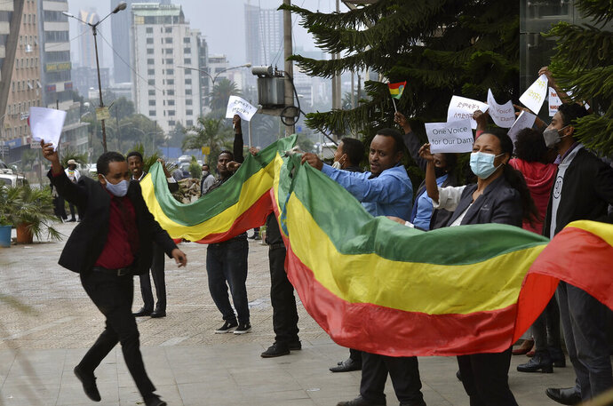 Ethiopians celebrate the progress made on the Nile dam, in Addis Ababa, Ethiopia, Sunday Aug. 2, 2020. Ethiopians in the capital celebrated the progress in the construction of the country's dam on the Nile River, which has caused regional controversy over its filling. In joyful demonstrations urged by posts on social media and apparently endorsed by the government, tens of thousands of residents flooded the streets of the capital Addis Ababa on Sunday afternoon, waving Ethiopia's flag and holding up posters. (AP Photo/Samuel Habtab)