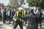 A teacher wearing a yellow vest is confronted by security forces during a demonstration in Rabat, Morocco, Wednesday, Feb. 20, 2019. Moroccan police fired water cannons at protesting teachers who were marching toward a royal palace and beat people with truncheons amid demonstrations around the capital Wednesday. (AP Photo/Mosa'ab Elshamy)