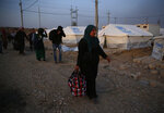 Syrians who are newly displaced by the Turkish military operation in northeastern Syria, carry their belongings as they walk to receive their tents, at the Bardarash camp, north of Mosul, Iraq, Wednesday, Oct. 16, 2019. The camp used to host Iraqis displaced from Mosul during the fight against the Islamic State group and was closed two years ago. The U.N. says more around 160,000 Syrians have been displaced since the Turkish operation started last week, most of them internally in Syria. (AP Photo/Hussein Malla)