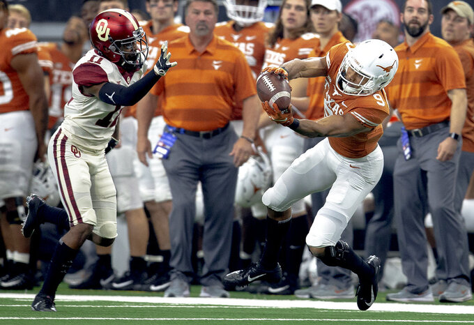 Texas wide receiver Collin Johnson (9) catches a pass in front of Oklahoma cornerback Parnell Motley (11) during the Big 12 Conference championship NCAA college football game in Arlington, Texas, on Saturday, Dec. 1, 2018.  (Nick Wagner/Austin American-Statesman via AP)