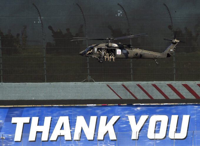 A Blackhawk helicopter carrying soldiers flies past a video screen during activities before a NASCAR Cup Series auto race at Charlotte Motor Speedway in Concord, N.C., Sunday, May 26, 2019. (AP Photo/Mike McCarn)