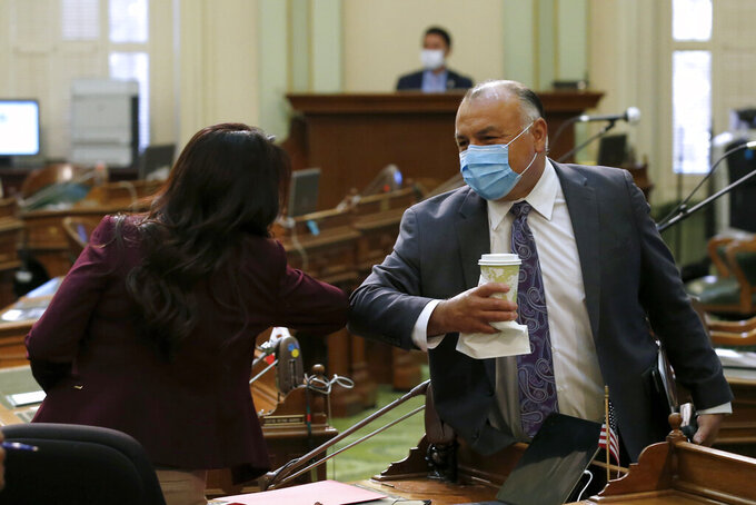 """Democratic Assembly members Blanca Rubio, left and Freddie Rodriquez, right, greet each other with elbow bumps at the Capitol in Sacramento, Calif., Tuesday, May 26, 2020. The Assembly met as a """"Committee of the Whole on the State Budget"""" to question Gov. Gavin Newsom's administration about its spending plan and how to fill an estimated $54.3 budget deficit because of the coronavirus. (AP Photo/Rich Pedroncelli, Pool)"""