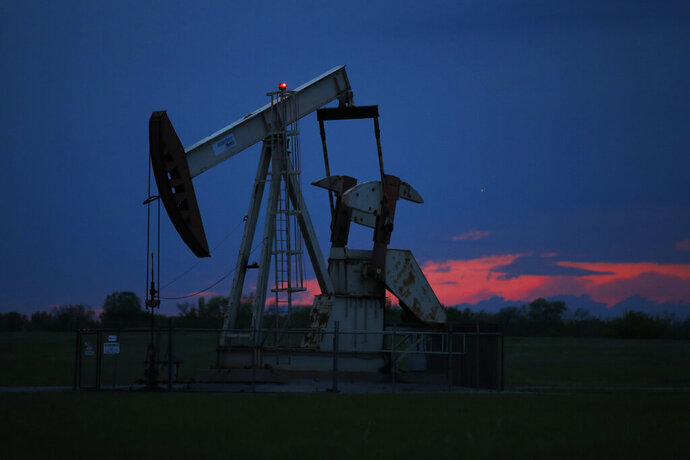 FILE In this April 21, 2020 file photo, a pumpjack is pictured as the sun sets in Oklahoma City.  Google says it won't build custom artificial intelligence tools for speeding up oil and gas extraction, taking an environmental stance that distinguishes it from cloud computing rivals Microsoft and Amazon.  The announcement followed a Greenpeace report on Tuesday, May 19,  that documents how the three tech giants are using AI and computing power to help oil companies find and access oil and gas deposits in the U.S. and around the world. (AP Photo/Sue Ogrocki File)
