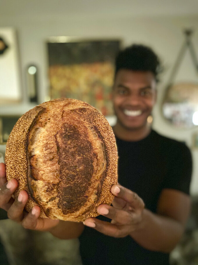 "Broadway performer Max Kumangai holds a loaf of sourdough bread at his apartment in New York. The triple threat from the musical ""Jagged Little Pill"" has leaned into a fourth skill as the pandemic marches on: baking and selling his own sourdough. (Michael Lowney/Humpday Dough via AP)"