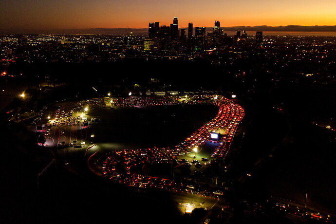 FILE - In this Nov 18, 2020, file aerial photo, motorists wait in long lines to take a coronavirus test in a parking lot at Dodger Stadium in Los Angeles. The Los Angeles County has announced a new stay-home order as coronavirus cases surge out of control in the nation's most populous county. The three-3 week order take effect Monday, Nov. 30, 2020.  The order advises residents to stay home
