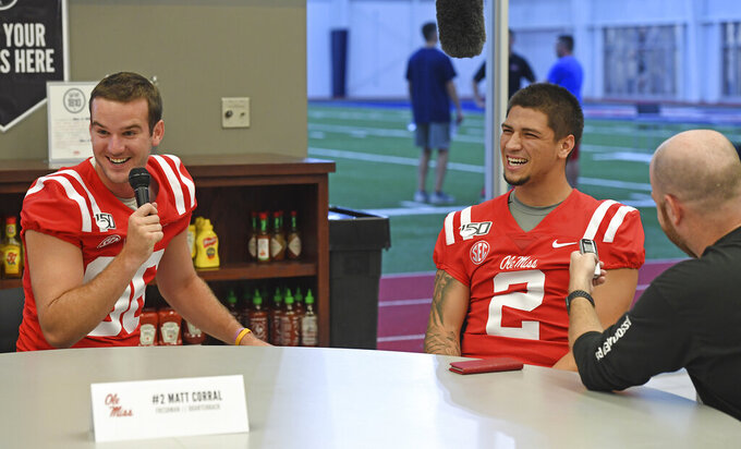 Mississippi holder Mack Brown, left, interviews quarterback Matt Corral during Mississippi's Media Day at the Manning Center in Oxford, Miss. on Thursday, Aug. 1, 2019. Mississippi begins NCAA college football practice on Friday and opens the season against Memphis on Aug. 31, 2019.  (AP Photo/Thomas Graning)