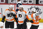 Philadelphia Flyers center Sean Couturier (14) celebrates his first goal of an NHL hockey game with right wing Jakub Voracek (93) and left wing Michael Raffl (12) during the third period against the Washington Capitals, Sunday, Feb. 7, 2021, in Washington. (AP Photo/Nick Wass)