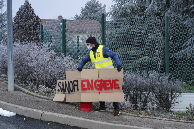 """A worker install a poster reading """"Sanofi on strike"""" outside the French pharmaceutical company Sanofi headquarters in Marcy l'Etoile, central France, Tuesday, Jan.19, 2021. Employees of pharmaceutical company Sanofi stage a protest against planned redundancies that they say could slow the fight against the Coronavirus pandemic . Sanofi had been developing Covid vaccines but will not be ready to roll out until late 2021. (AP Photo/Laurent Cipriani)"""