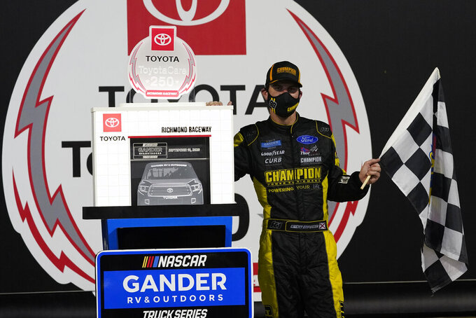 Grant Enfinger poses with the winner's trophy as he celebrates after winning a NASCAR Truck Series auto race Thursday, Sept. 10, 2020, in Richmond, Va. (AP Photo/Steve Helber)