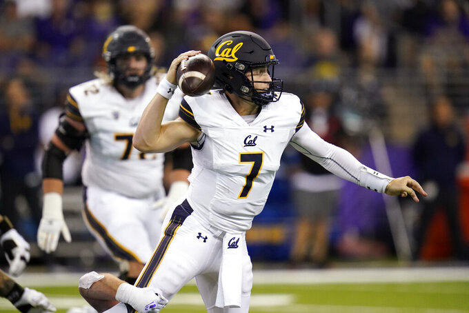 California quarterback Chase Garbers (7) gets a pass off under pressure in the first half of an NCAA college football game against Washington, Saturday, Sept. 25, 2021, in Seattle. (AP Photo/Elaine Thompson)