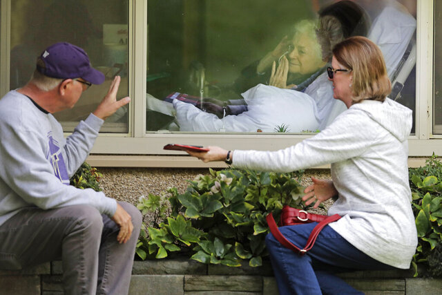 Judie Shape, center, who has tested positive for the coronavirus, blows a kiss to her son-in-law, Michael Spencer, left, as Shape's daughter, Lori Spencer, right, looks on, Wednesday, March 11, 2020, as they visit on the phone and look at each other through a window at the Life Care Center in Kirkland, Wash., near Seattle. In-person visits are not allowed at the nursing home.  The vast majority of people recover from the new coronavirus. According to the World  Health Organization, most people recover in about two to six weeks, depending on the severity of the illness. (AP Photo/Ted S. Warren)