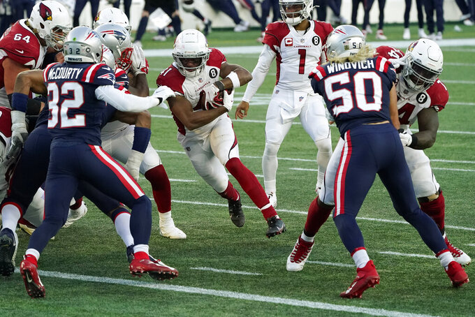 Arizona Cardinals running back Kenyan Drake, center, runs for a touchdown as New England Patriots defenders Devin McCourty, left, and Chase Winovich, right, pursue in the second half of an NFL football game, Sunday, Nov. 29, 2020, in Foxborough, Mass. (AP Photo/Charles Krupa)