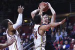 Virginia guard Kody Stattmann, right, shoots over Boston College guard Chris Herren Jr. (24) during the first half of an NCAA college basketball game Tuesday, Jan. 7, 2020 in Boston. (AP Photo/Charles Krupa)