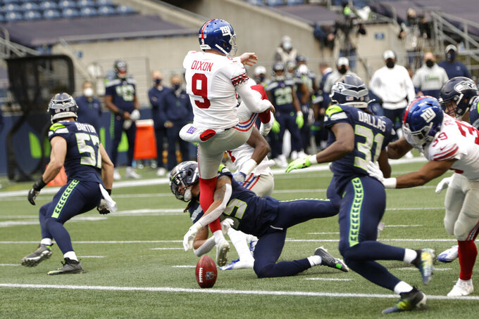New York Giants punter Riley Dixon (9) has a punt blocked by Seattle Seahawks cornerback Ryan Neal (35), center, for a safety during the first half of an NFL football game, Sunday, Dec. 6, 2020, in Seattle. (AP Photo/Larry Maurer)