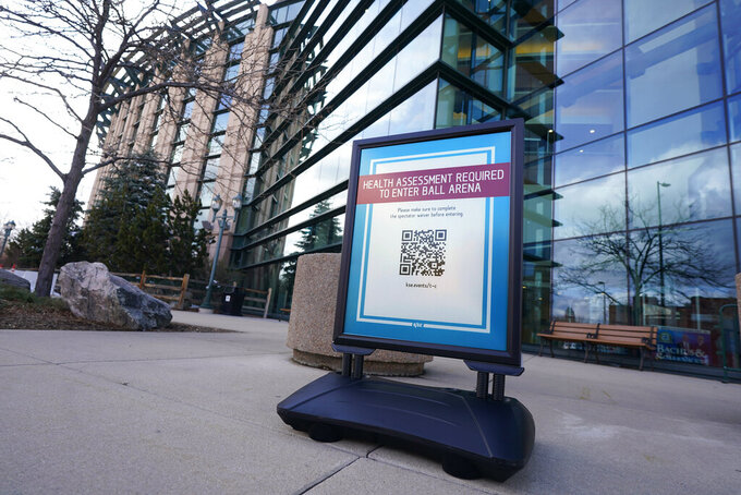 A sign reminds fans, who are being allowed into Ball Arena for the first time in more than a year because of the coronavirus, to fill out their health assessment before entering to watch the Philadelphia 76ers face theDenver Nuggets in the first half of an NBA basketball game Tuesday, March 30, 2021, in Denver. (AP Photo/David Zalubowski)