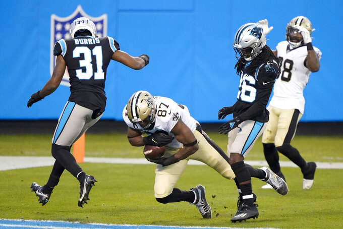 New Orleans Saints tight end Jared Cook scores between Carolina Panthers strong safety Juston Burris, left, and cornerback Donte Jackson during the first half of an NFL football game Sunday, Jan. 3, 2021, in Charlotte, N.C. (AP Photo/Brian Blanco)