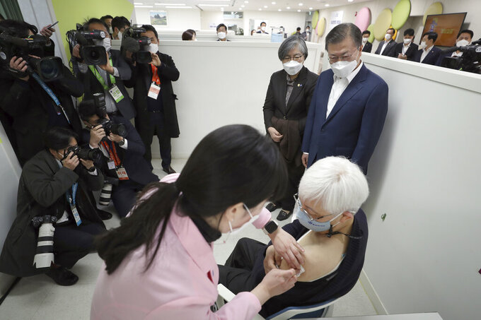 South Korean President Moon Jae-in, top right, watches a doctor receives a shot of AstraZeneca vaccine at a public health center in Seoul, South Korea, Friday, Feb. 26, 2021. South Korea on Friday administered its first available shots of coronavirus vaccines to people at long-term care facilities, launching a mass immunization campaign that health authorities hope will restore some level of normalcy by the end of the year. (Choe Jae-koo/Yonhap via AP)