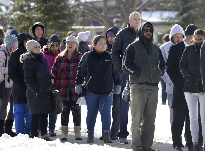 Parents wait in line to be reunited with students at the Tipler Middle school reunification center on Tuesday December 3, 2019, in Oshkosh, Wis. Earlier, police responded to an officer invloved shooting at Oshkosh West High School after an armed student confronted a school resource officer. (Wm. Glasheen/The Post-Crescent via AP)