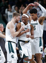 Michigan State's Kyle Ahrens, left, Cassius Winston, center, and Malik Hall celebrate during the second half of an NCAA college basketball game against Iowa, Tuesday, Feb. 25, 2020, in East Lansing, Mich. Michigan State won 78-70. (AP Photo/Al Goldis)