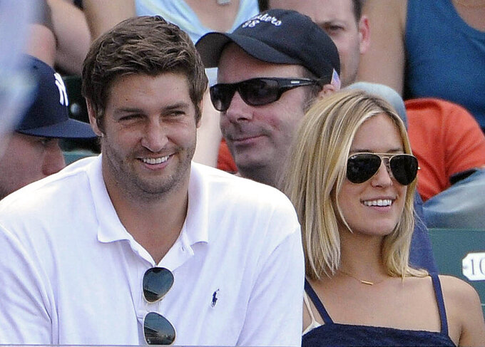 FILE - In this July 2, 2011, file photo, Chicago Bears quarterback Jay Cutler, left, and his wife Kristin Cavallari watch the Chicago Cubs play the Chicago White Sox during an interleague baseball game in Chicago. Reality TV star Cavallari and former Chicago Bears quarterback Cutler are getting divorced. Cavallari announced Sunday, April 26, 2020, in an Instagram post that the couple are breaking up after after seven years of marriage and a decade together. (AP Photo/Brian Kersey, File)