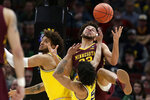Minnesota's Gabe Kalscheur, right, battles for a rebound against Michigan's Eli Brooks and Isaiah Livers, left, during the first half of an NCAA college basketball game in the semifinals of the Big Ten Conference tournament, Saturday, March 16, 2019, in Chicago. (AP Photo/Kiichiro Sato)