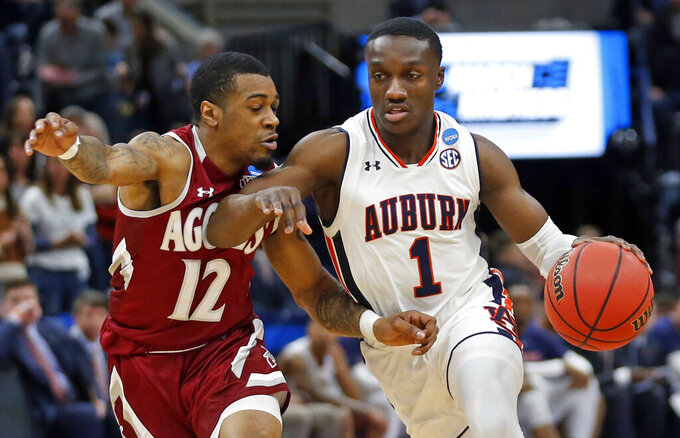 Auburn Tigers guard Jared Harper (1) drives as New Mexico State guard AJ Harris (12) defends in the first half during a first round men's college basketball game in the NCAA Tournament, Thursday, March 21, 2019, in Salt Lake City. (AP Photo/Rick Bowmer)