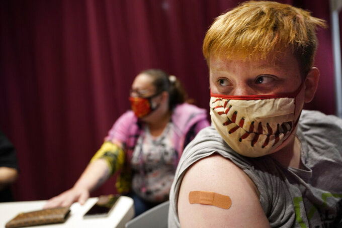 Jacob Conary, 15,  listens to advice from a medical assistant after receiving his first shot of the COVID-19 vaccination, Wednesday, May 12, 2021, in Auburn, Maine. Vaccination clinics in Maine recently opened up to 12 to 15-year-olds. (AP Photo/Robert F. Bukaty)