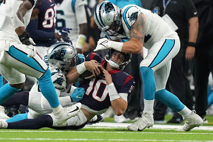 Houston Texans quarterback Davis Mills (10) is tackled by Carolina Panthers' Haason Reddick (43) and Morgan Fox (91) during the first half of an NFL football game Thursday, Sept. 23, 2021, in Houston. (AP Photo/Eric Christian Smith)
