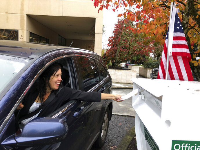 FILE - In this Nov. 6, 2018 file photo, a voter in Lake Oswego, Ore., places her ballot in a designated drop box outside City Hall. Two Oregon counties are offering the opportunity for U.S. military members, their dependents and others living overseas to vote in special elections this November with smartphones (AP Photo/Gillian Flaccus, File)