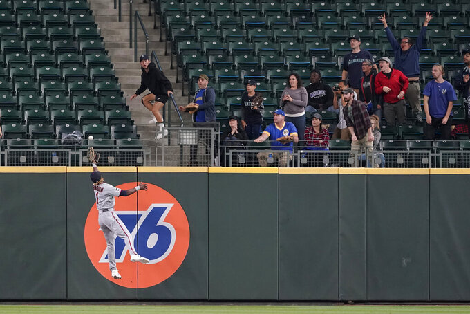 Seattle Mariners fans react as Minnesota Twins center fielder Nick Gordon leaps but can't catch a go-head solo home run hit by Seattle Mariners' Jake Bauers during the eighth inning of a baseball game, Monday, June 14, 2021, in Seattle. (AP Photo/Ted S. Warren)