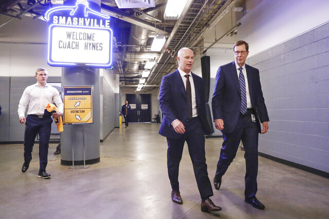 New Nashville Predators NHL hockey team head coach John Hynes, second from right, walks to a news conference with Predators general manager David Poile, right, on Tuesday, Jan. 7, 2020, in Nashville, Tenn. The Predators hired Hynes, the former New Jersey Devils coach, as the third coach in franchise history after firing Peter Laviolette. (AP Photo/Mark Humphrey)