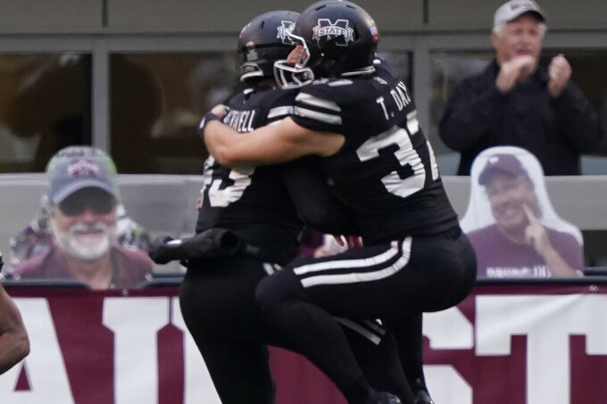 Mississippi State safety Paul Blackwell, left, and punter Tucker Day celebrate Blackwell's fumble recovery for a touchdown during the first half of an NCAA college football game, Saturday, Dec. 19, 2019, in Starkville, Miss. (AP Photo/Rogelio V. Solis)