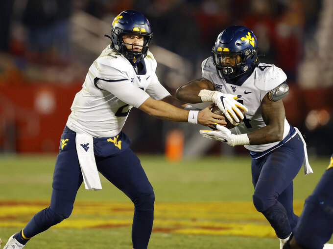 West Virginia quarterback Jarret Doege, left, hands off to running back Leddie Brown during the second half of the team's NCAA college football game against Iowa State, Saturday, Dec. 5, 2020, in Ames, Iowa. (AP Photo/Matthew Putney)